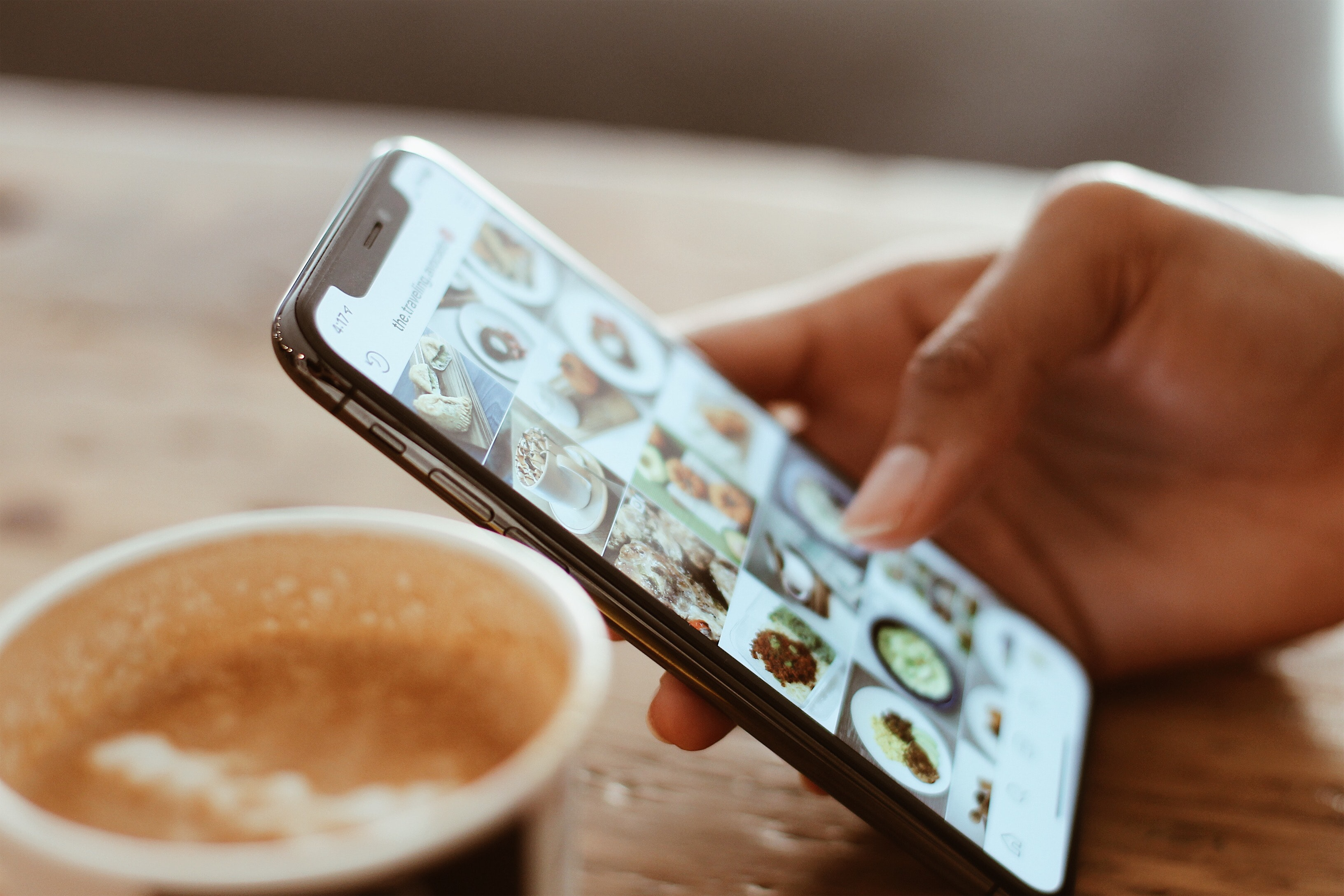 Social media marketing calgary picture of a phone someone on instagram with a coffee next to them